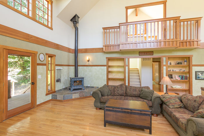 Great Room with deck access, built-ins, wood stove and balcony