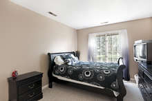 Located on the entry level, this carpeted bedroom has its own attached bath, as well as oversized windows and a large closet. 