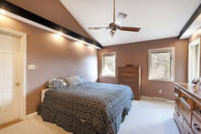 Sweeping vaulted ceilings rise over the master bedroom. The room has two closets, including a walk-in. Recessed lighting mounted on both walls gives the room a modern feel. The door on the left leads to an unfinished attic with great potential. 