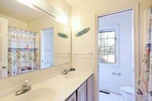 This full bath has a long vanity with double sinks and wood cabinets, as well as a tub shower. 