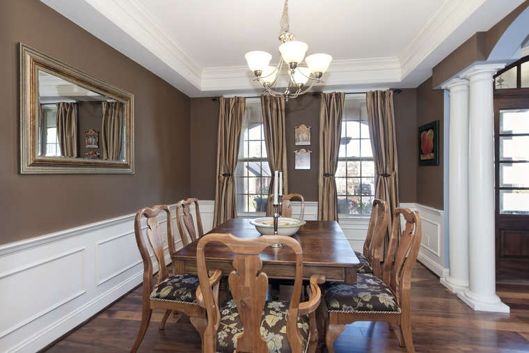Classic Wainscoting Hardwood Floors And A Tray Ceiling Lend Regal Impression To The