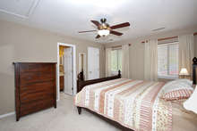 A view of the carpeted master suite, which has a walk-in-closet and ceiling fan. Large windows keep the room bright.