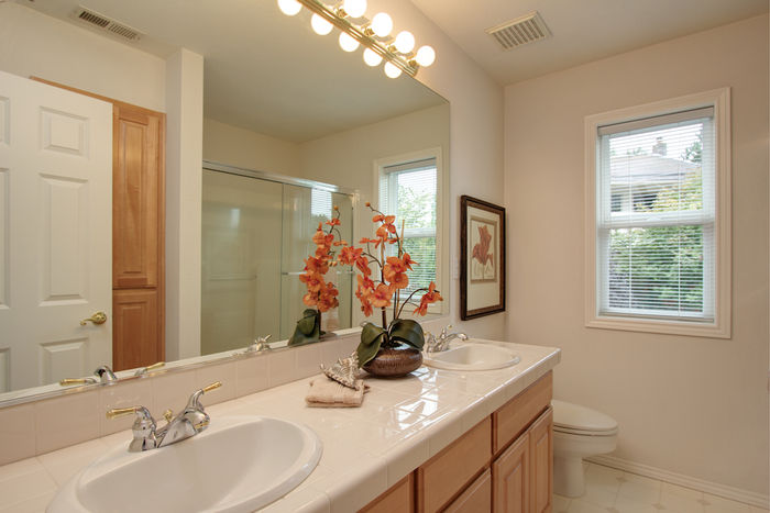 Upper bathroom with dual sinks & glass bath door
