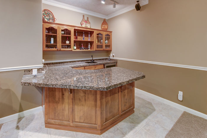 Wet bar in family room with granite counters